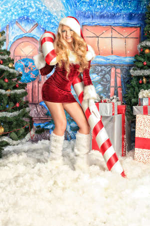 Beautiful young woman in Santa Claus clothes over Christmas background. Stock Photo - 10978417