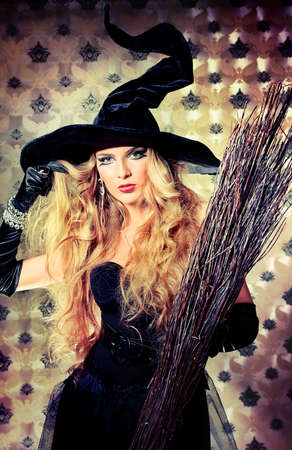 Charming halloween witch with broom over vintage background. Stock Photo - 10978367