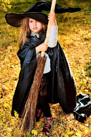 Shot of a little girl in halloween costume posing with broom and pumpkin outdoor. photo