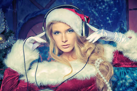 Beautiful young woman in Santa Claus clothes and headphones over Christmas background. Stock Photo