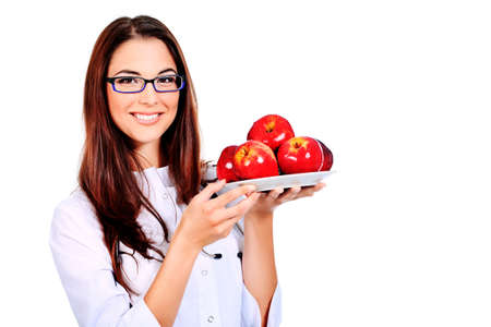 Portrait of a beautiful woman doctor holding a plate of apples. Isolated over white background. photo