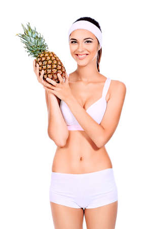 Portrait of a beautiful young woman fresh pineapple. Isolated over white background. photo