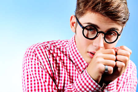 Portrait of a funny young man in spectacles. Over grey background. photo