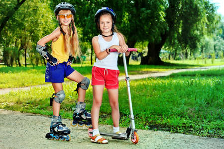 vespa: Chicas felices con rodillos y scooter en un parque de verano.