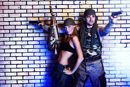 army girl: Shot of a military couple posing against brick wall. Stock Photo