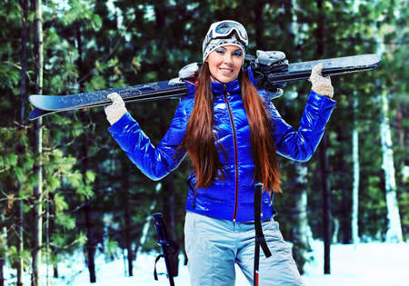 downhill: Sporty young woman posing with her skis outdoor. Stock Photo