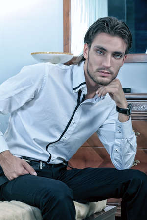 Portrait of a handsome fashionable man posing in the interior. photo