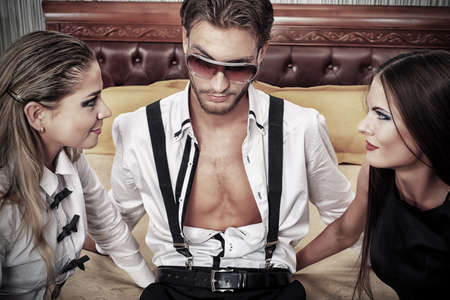 Portrait of a handsome fashionable man with two charming women posing in the interior. Imagens