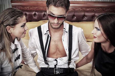 donne eleganti: Ritratto di un uomo bello, alla moda con due donne affascinanti posa in interni.