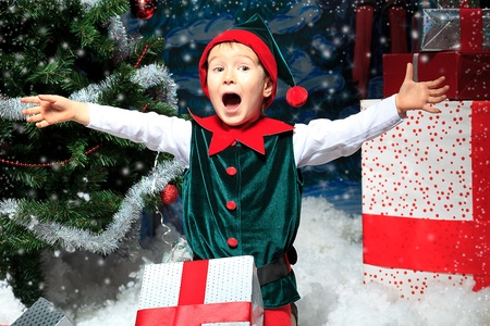christmas toy: Little boy in Christmas elf costume posing over christmas background.