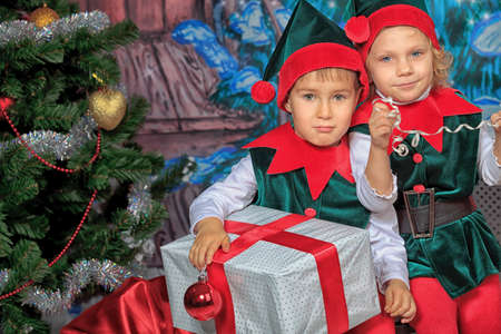 Two cute children in christmas elf costumes posing over christmas background. Stock Photo - 11044282