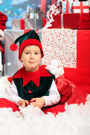 Little boy in Christmas elf costume posing over christmas background. Stock Photo - 11044271