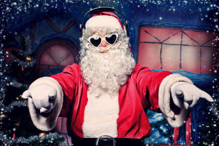 christmas costume: Santa Claus is listening to music in headphones. Christmas. Stock Photo