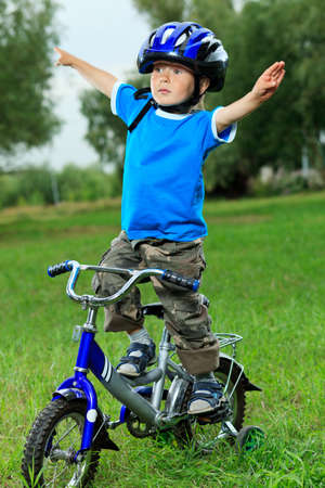 bike trail: Happy boy on a bicycle in a summer park. Stock Photo