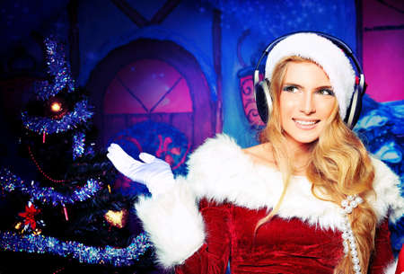 Beautiful young woman in Santa Claus clothes and headphones over Christmas background. Stock Photo - 11185342