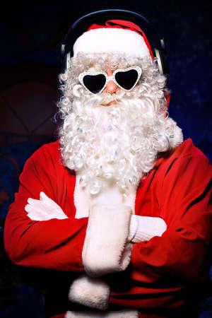 audifonos dj: Santa Claus está escuchando música en los auriculares. Navidad.