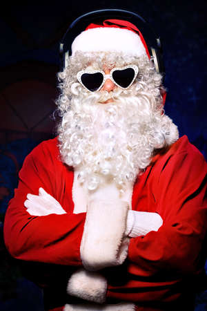 snow man party: Santa Claus is listening to music in headphones. Christmas. Stock Photo
