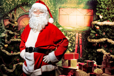 Santa Claus posing with presents over Christmas background. Stock Photo - 11185265