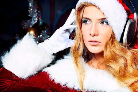 claus: Joven y bella mujer de Santa Claus ropa y los auriculares sobre fondo de Navidad. Foto de archivo