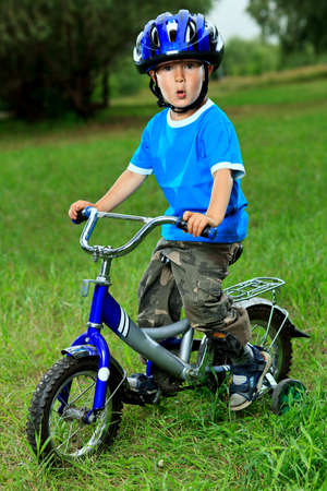trail bike: Happy boy on a bicycle in a summer park. Stock Photo