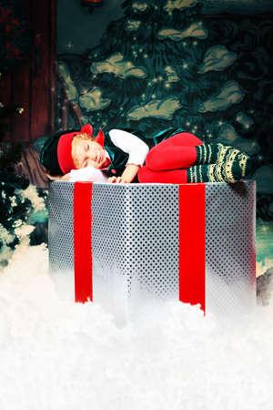 Little girl in Christmas elf costume posing over christmas background. photo