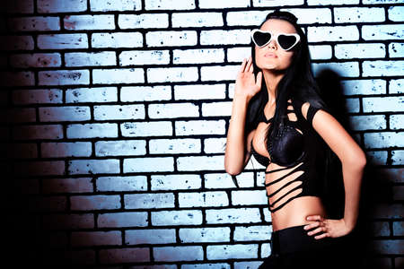 love hot body: Fashion photo, a model is posing over brick wall.