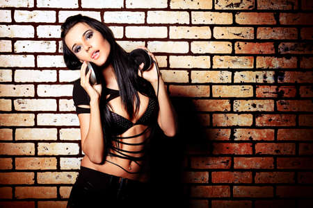 Fashion photo, a model is posing over brick wall. Stock Photo - 11185195