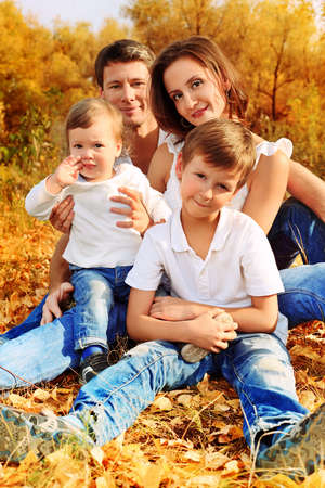 fall fun: Happy family having a rest outdoor in the autumn park. Stock Photo