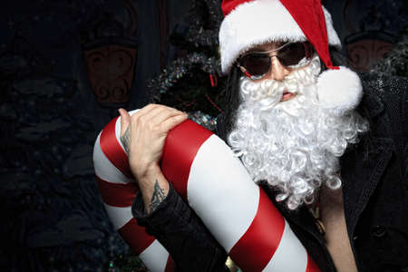 Portrait of a funny young man in Santa Claus hat and beard. Christmas. Stock Photo - 11185207