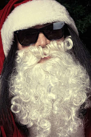 Portrait of a funny young man in Santa Claus hat and beard. Christmas. photo