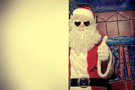 christmas costume: Party Santa Claus holding white board over Christmas background.