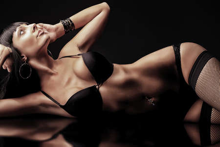 Shot of a sexy woman in black lingerie over black background. Stock Photo - 11261480
