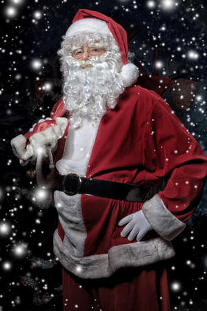 nick: Santa Claus posing with presents over dark background. Stock Photo