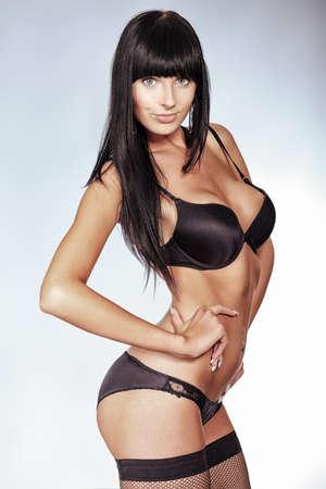 sexy girl nue: Tir d'une femme sexy en lingerie noire sur fond gris. Banque d'images