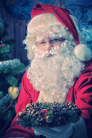 Santa Claus posing with presents over Christmas background. photo