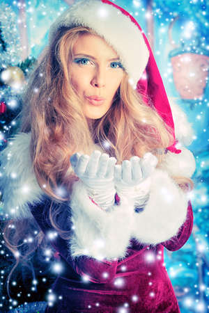 Beautiful young woman in Santa Claus clothes blowing snow. photo