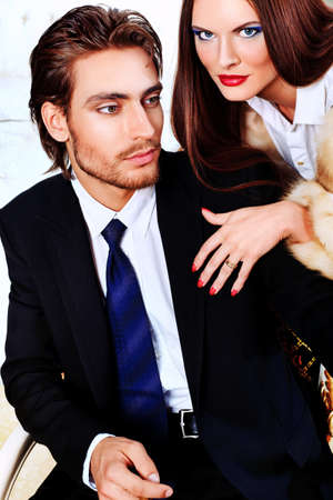 expensive: Portrait of a handsome fashionable man with  charming woman posing in the interior. Stock Photo