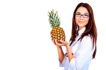 Portrait of a beautiful woman doctor holding pineapple. Isolated over white background. photo