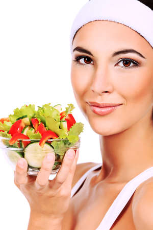 Portrait of a beautiful young woman eating vegetable salad. Isolated over white background. Stock Photo - 11261507