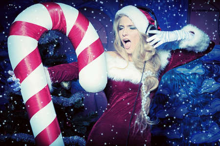 Beautiful young woman in Santa Claus clothes and headphones over Christmas background. Stock Photo - 11261505