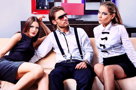 sexy love: Portrait of a handsome fashionable man with two charming women posing in the interior. Stock Photo