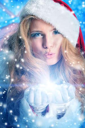 sexy santa girl: Beautiful young woman in Santa Claus clothes blowing snow.