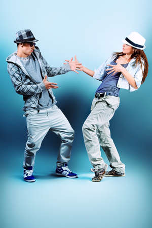 hands on hip: A couple of young man and woman dancing hip-hop at studio. Stock Photo