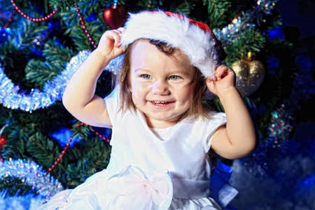 Beautiful child sitting against Christmas decoration. photo