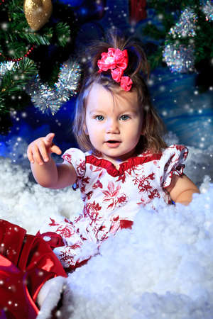 Beautiful child sitting against Christmas decoration. Stock Photo - 11261536