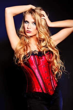 corsetto: Ritratto di una bella donna bionda su sfondo nero.