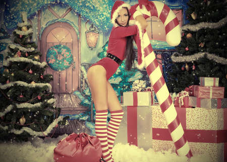 Beautiful young woman in Santa Claus clothes over Christmas background. Stock Photo - 11261573