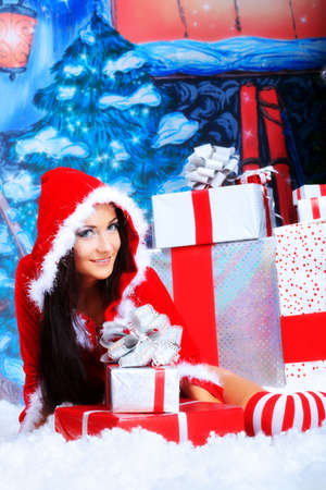 Beautiful young woman in Santa Claus clothes over Christmas background. Stock Photo - 11261565