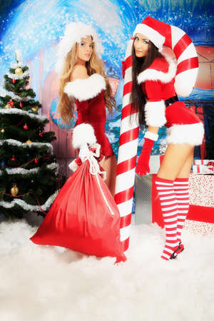 sexy santa m�dchen: Zwei sexy junge Frauen in Kleidern posieren �ber Weihnachten Weihnachten Hintergrund. Lizenzfreie Bilder