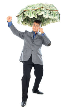 Business concept: businessman holding an umbrella of money. Isolated over white.  photo